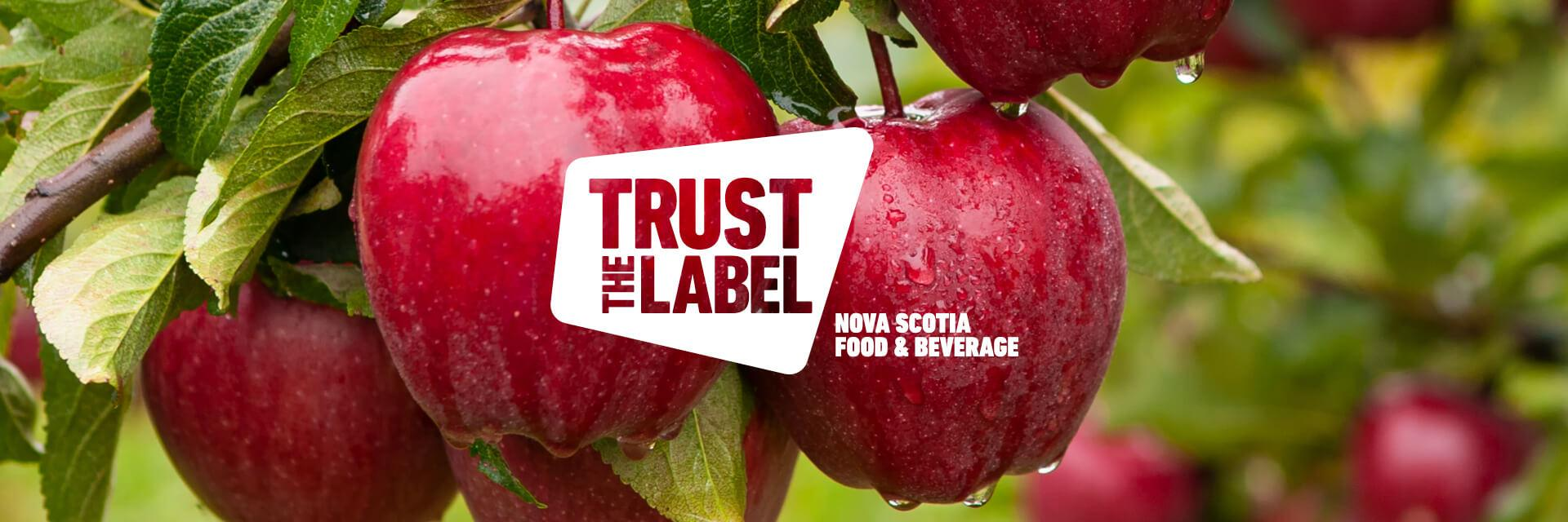 A 'Trust the Label' Nova Scotia Food and Beverage logo overlaid on a photo of red apples on a branch