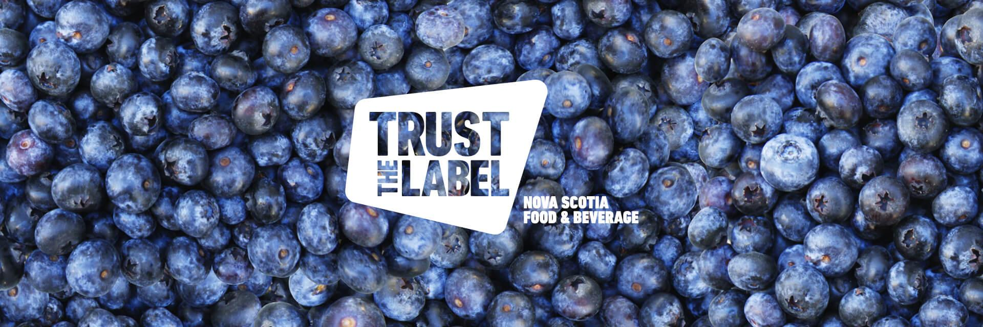 A 'Trust the Label' Nova Scotia Food and Beverage logo overlaid on a photo of blueberries.
