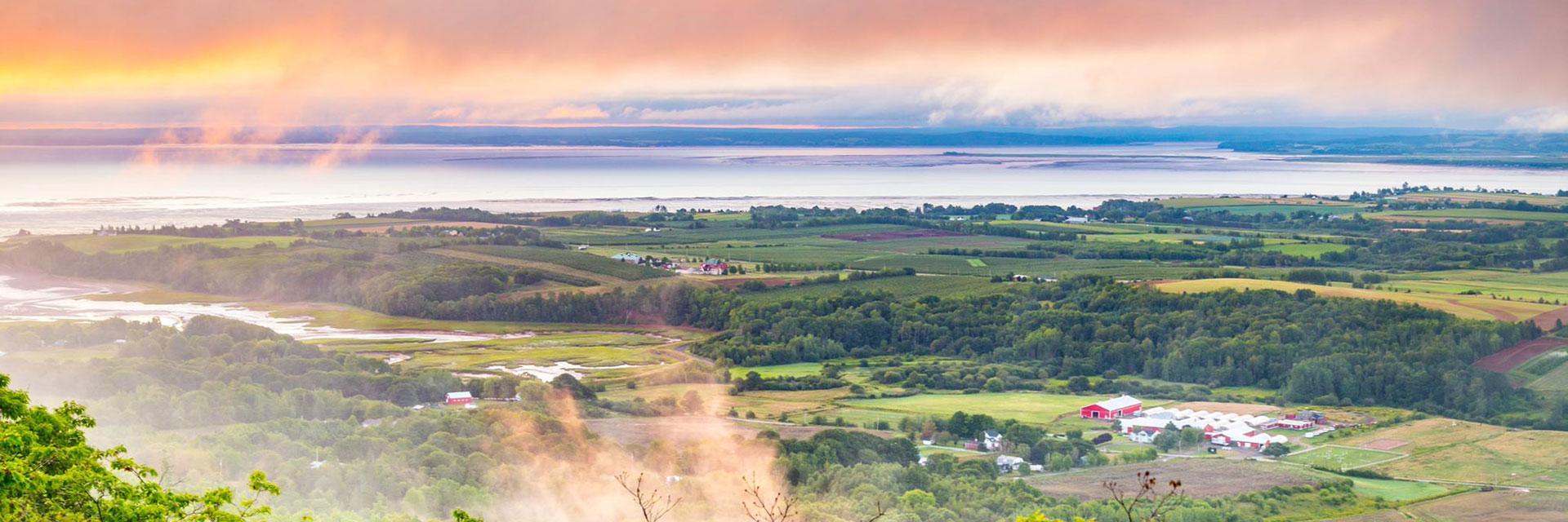 A scene overlooking rural Nova Scotia farmland and water with the sun and some clouds in the sky,