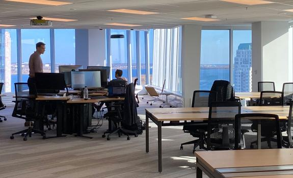 Workers standing in an office overlooking the Halifax Harbour