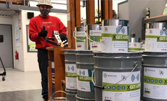 Worker standing behind stacked cans of Graphite Innovation & Technologies product