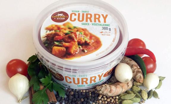 A container of Shivani's Kitchen curry surrounded by ingredients.