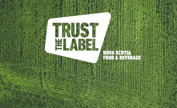 A 'Trust the Label' Nova Scotia Food and Beverage logo overlaid on an aerial photo of a green field of crops
