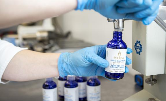 Person filling hand sanitizer product bottle in lab